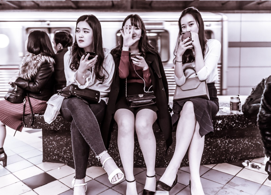 3 women sitting on a bench on the Red Line platform at Hollywood & Highland