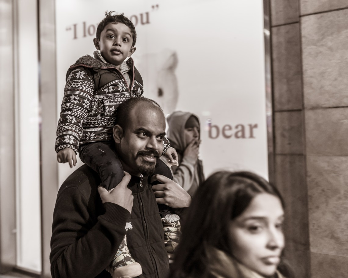 a young boy on a man's (his dad, presumably) shoulders, walking down Hollywood Boulevard