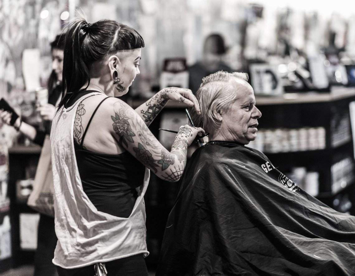 a man sits in a barber's chair as a woman cuts his hair. Cahuenga Blvd. Hollywood, Los Angeles, Califorina.