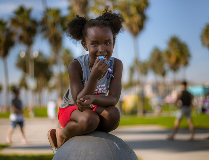 a young girl sits on top of a wide bollard near the Venice Beach Basketball Courts