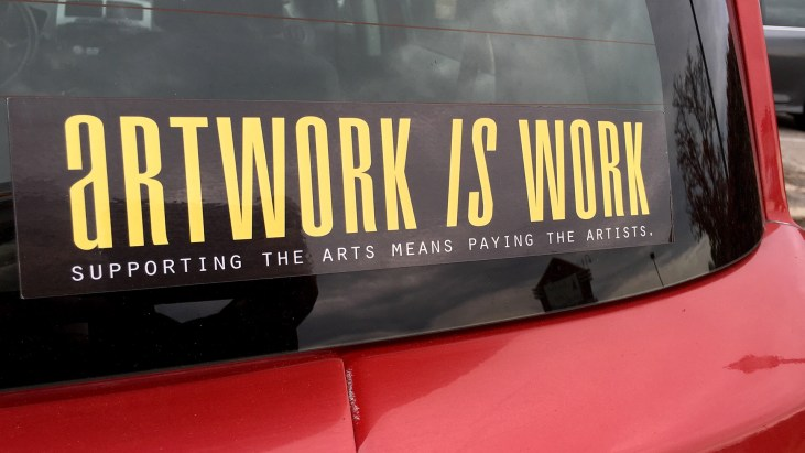 "photo of a car with a sticker on the window that reads, ""Artwork is work"""