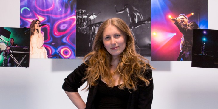 Julie Pavlacka standing in Gallery Xue in New Taipei. She stands in front of  a half dozen large prints of concert photography.