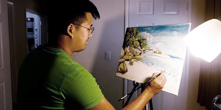photograph of painter Alex Wu at work in his studio
