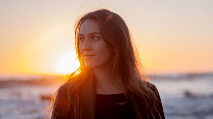 photo of artist Nicolette Cussins at the beach at sunset