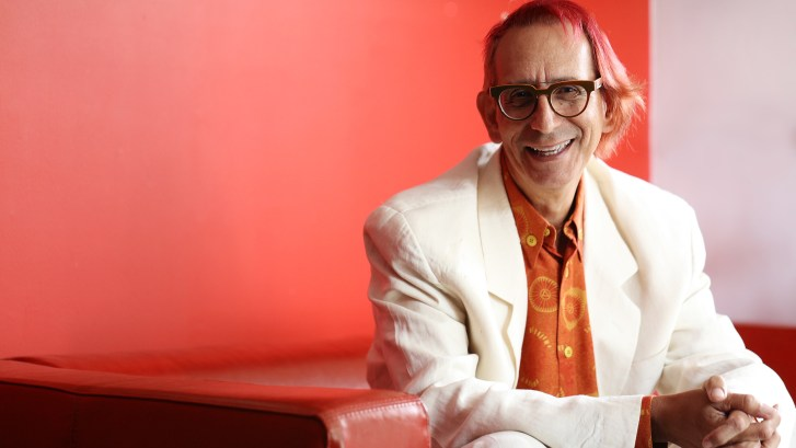 Photo of Glenn Zucman in a white suit and sitting on a red sofa
