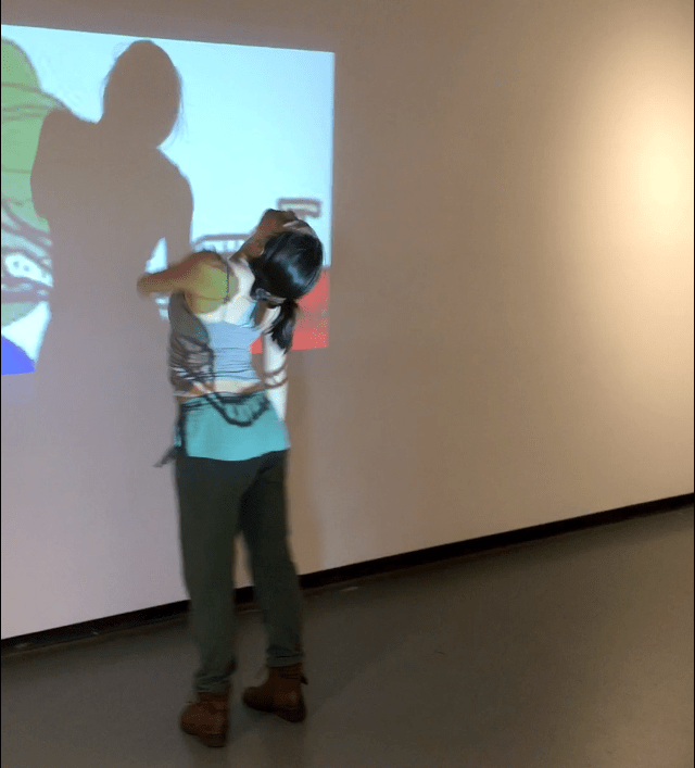 Toria Painter performs in the CSULB School of Art's Werby Gallery in response to a video projection in  Carmina Correa and Vanessa Olivarez' Meme group exhibition