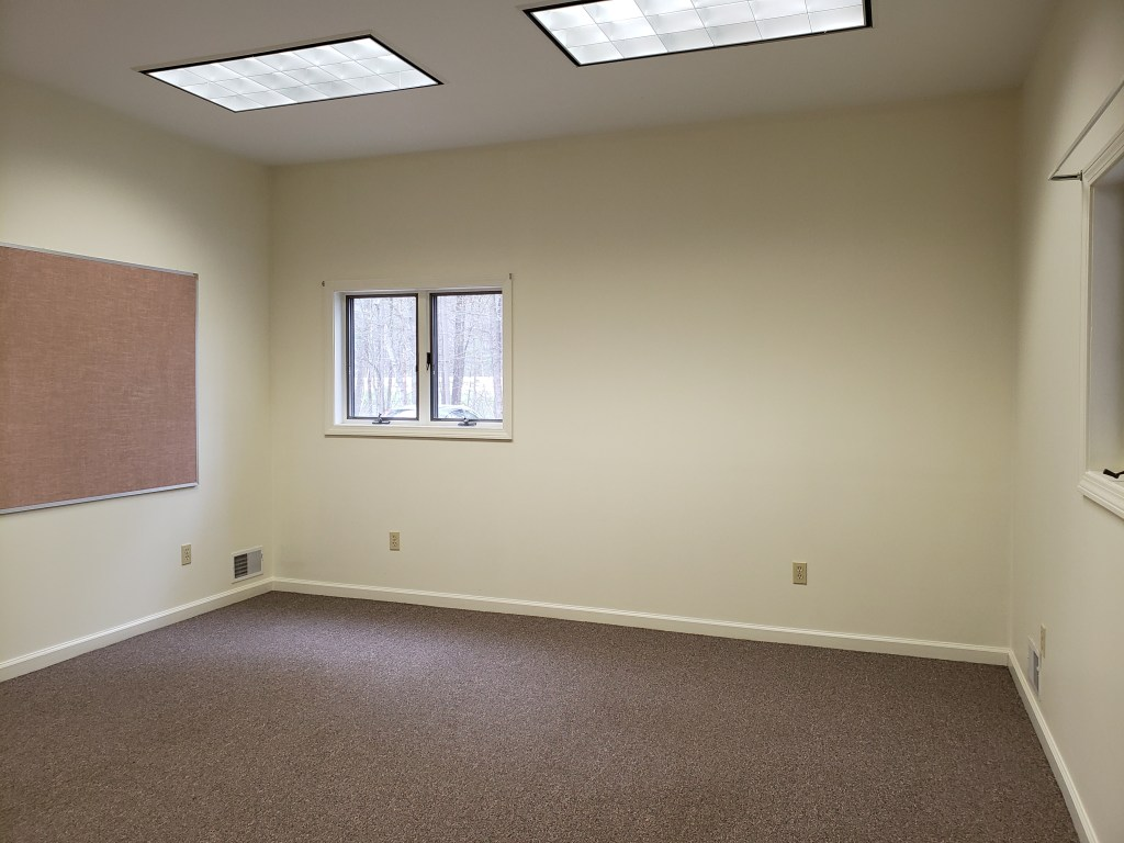 A room with white walls, dark colored carpeting and a small window.