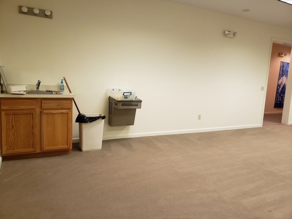 A wide room with white walls, tan carpeting, and a sink and drinking fountain in one corner.
