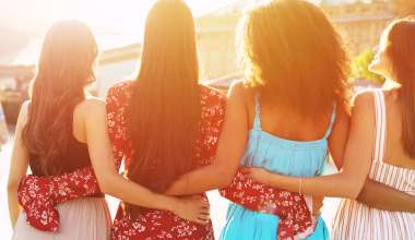 Four women standing together with their arms around each other's waist