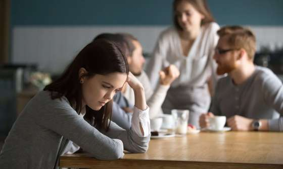 Sad woman sits at a table with her head resting on her hand while others chat happily behind her