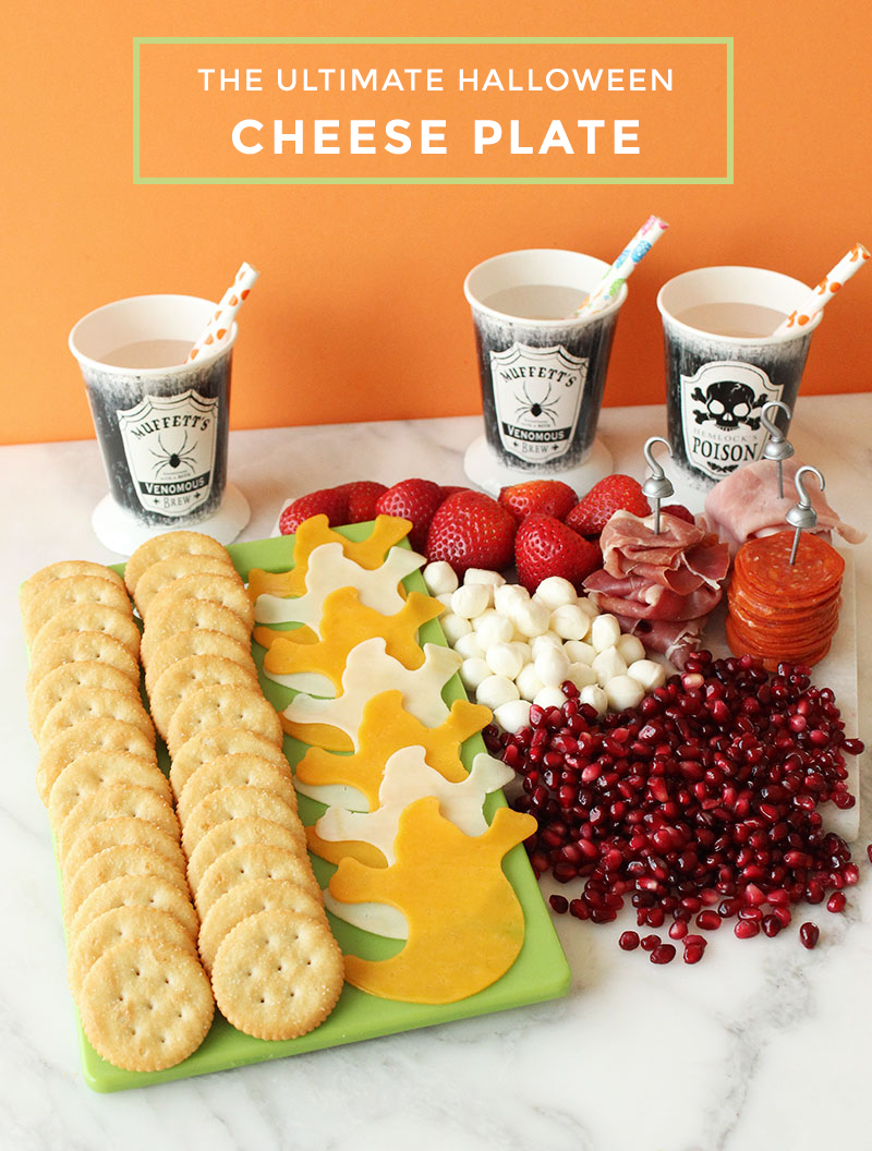 A kid friendly Halloween cheese plate with crackers, fruit, cheese and meat.