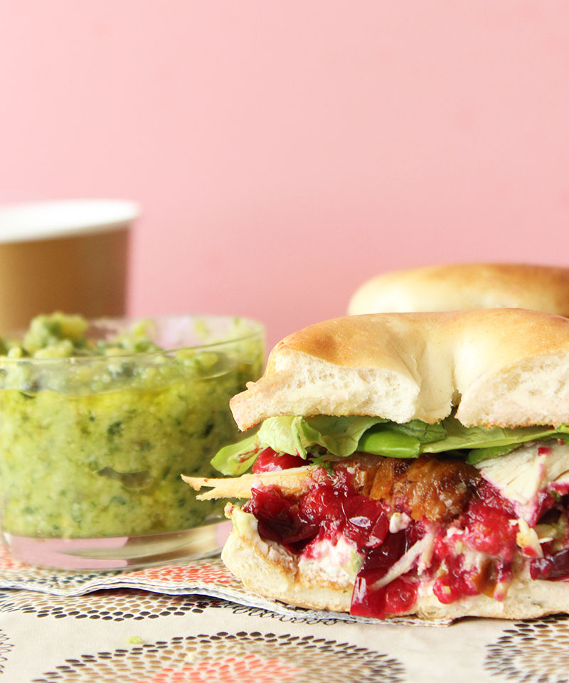 A mini bagel sandwich with pesto, cranberry and turkey.