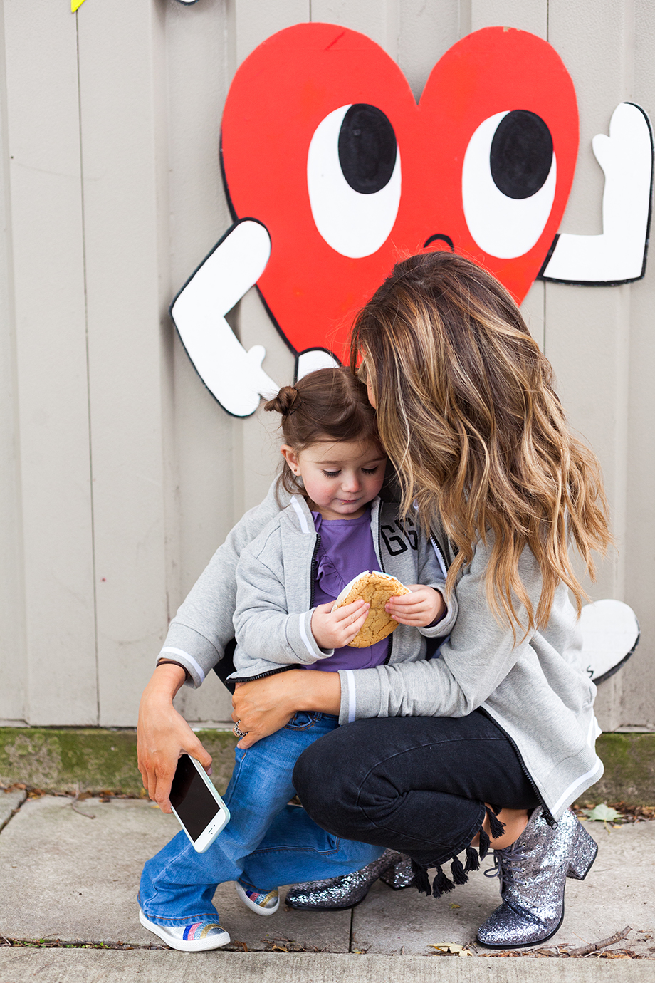 A mother and daughter wearing matching grey best friend varsity jackets in a Chicago street style snap.