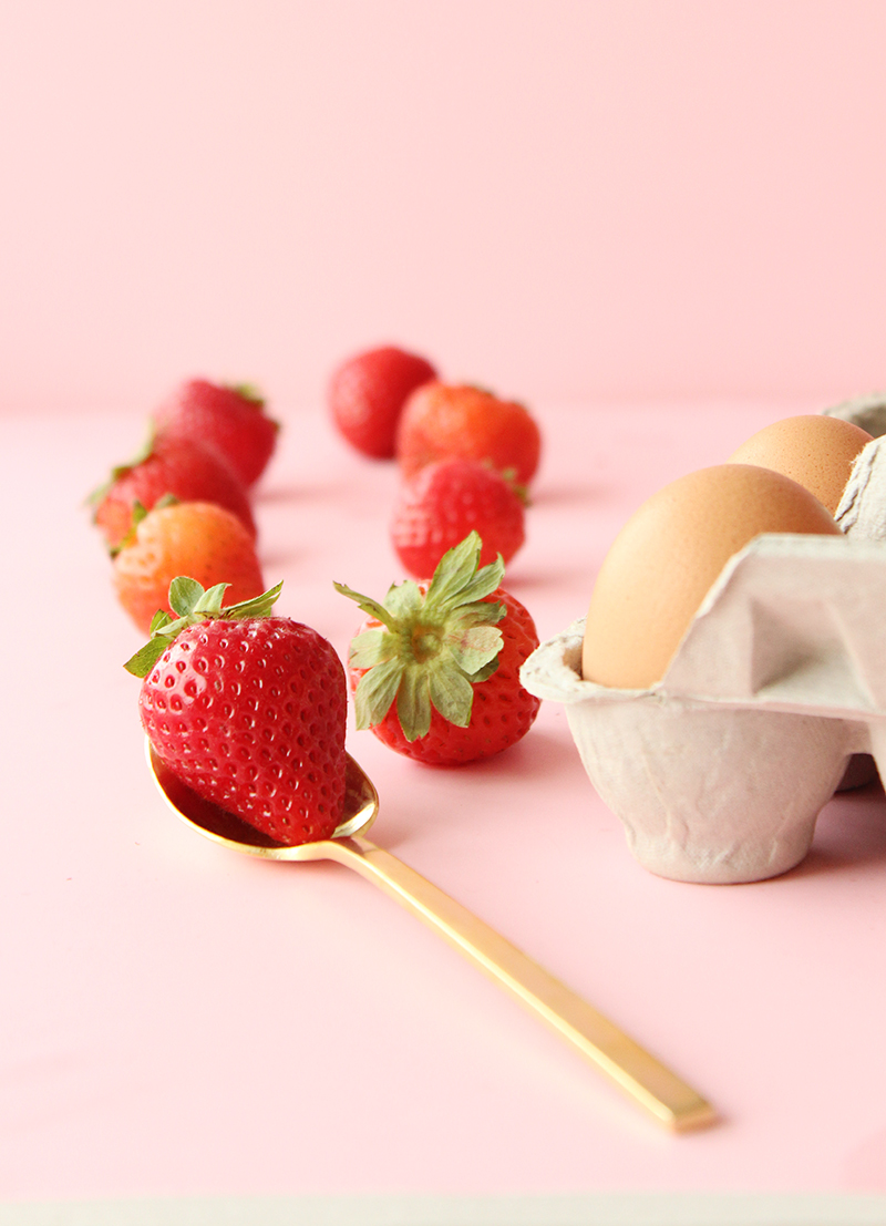 Strawberries and eggs with gold flatware.