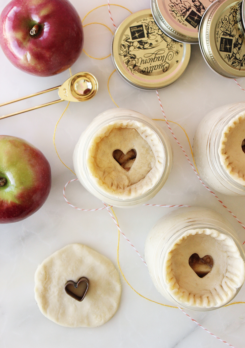 Mini apple pies in mason jars with hearts cut in the top of the dough.