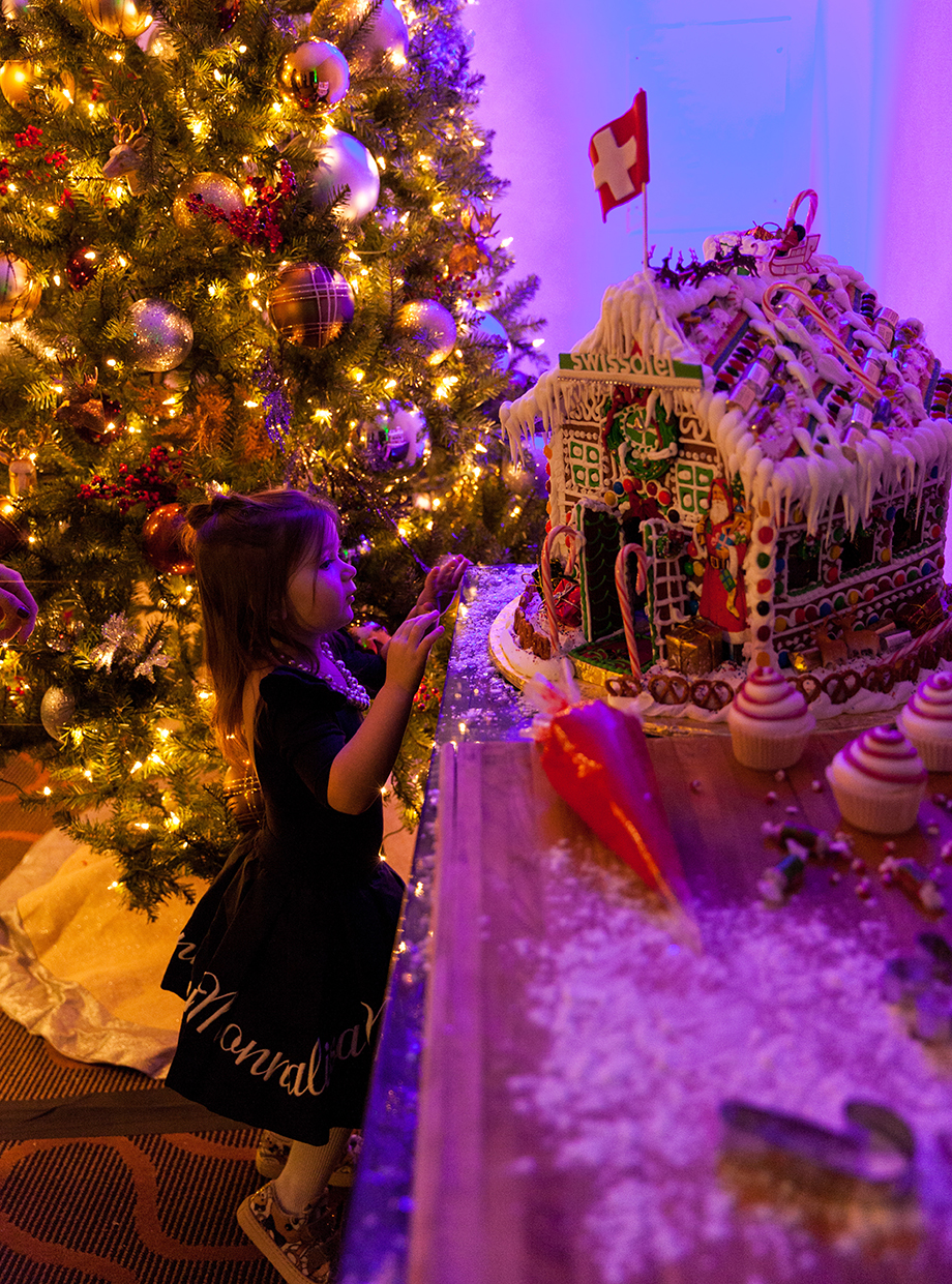 A little girl looks at a gingerbread house.