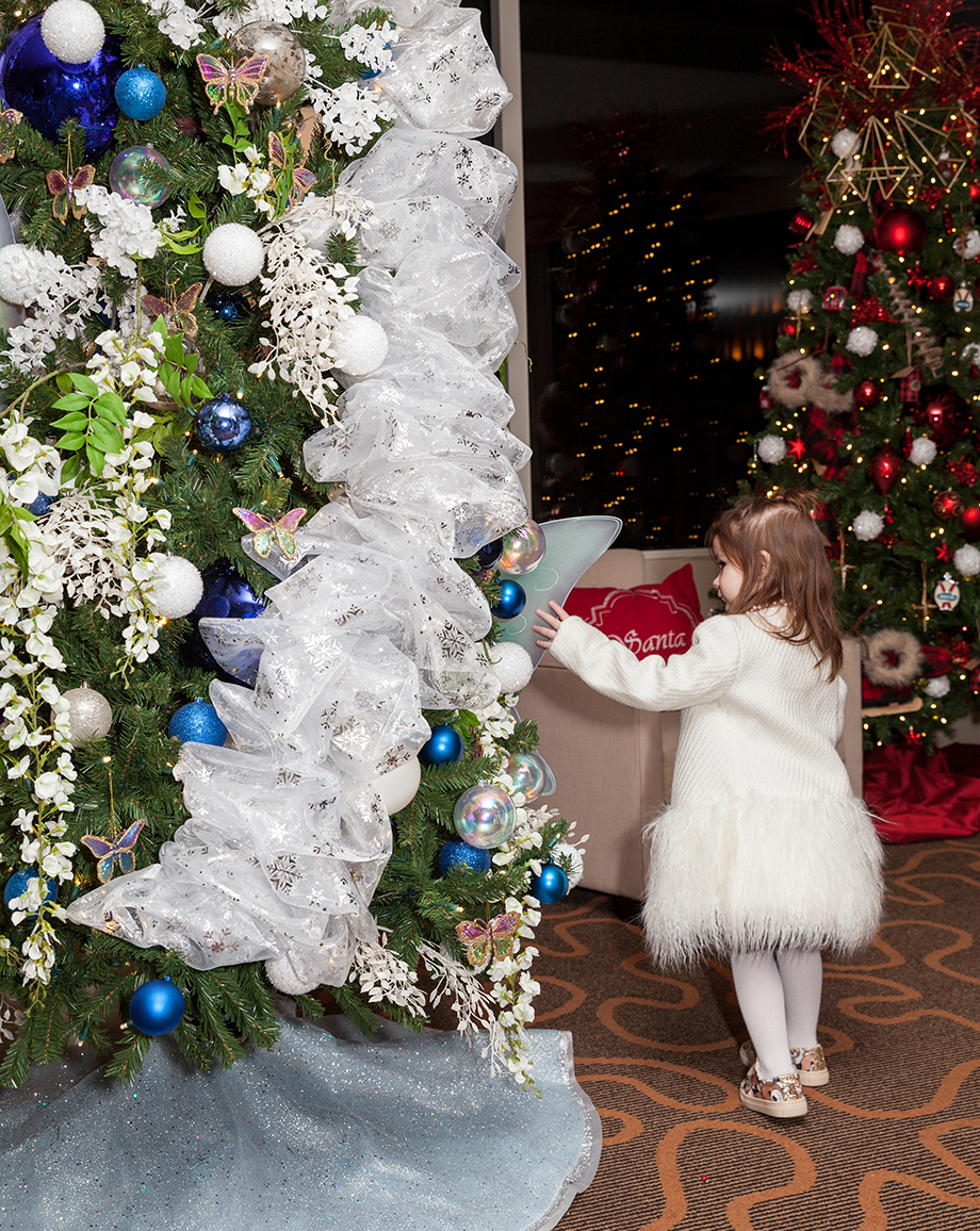 A little girl looking at Christmas trees in a white feather coat at the Swissotel in Chicago.