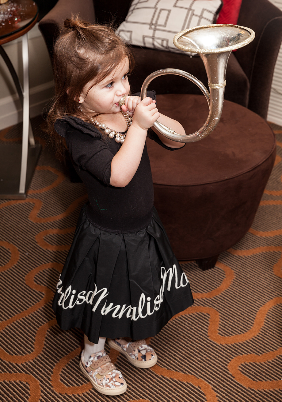 A little girl wears a full black skirt with a black jumpsuit.