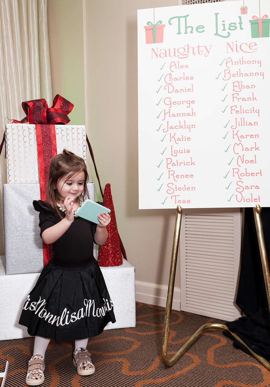 A little girl wearing a Mona Lisa outfit double checking Santa's list at the Swissotel in Chicago.