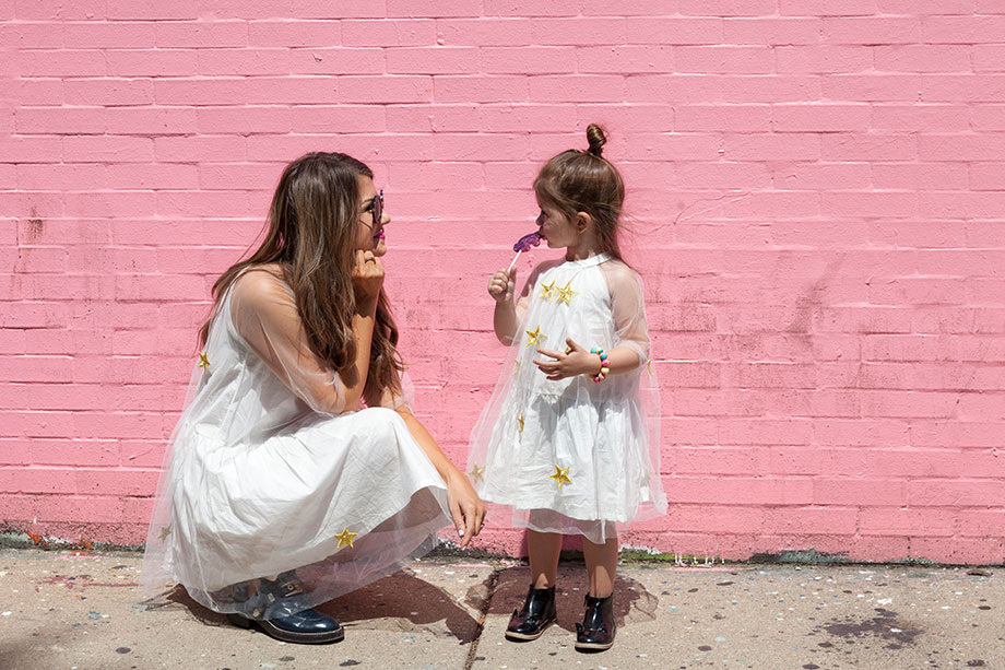 A mother daughter duo wearing matching star print dresses.