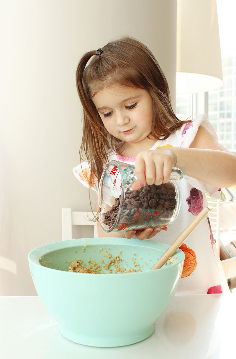 Pouring chocolate chips into cookie dough batter.