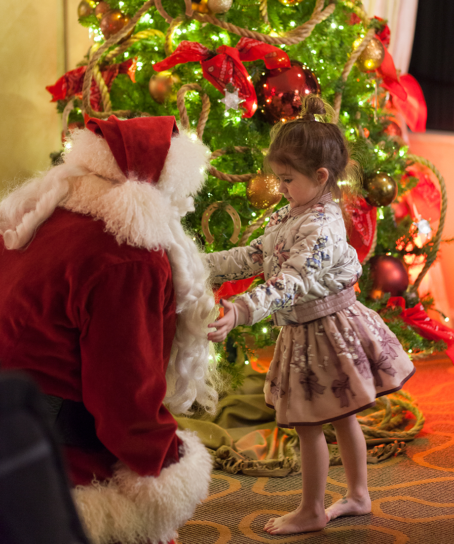 A little girl wearing Monnalisa stands with Santa by the Christmas tree.