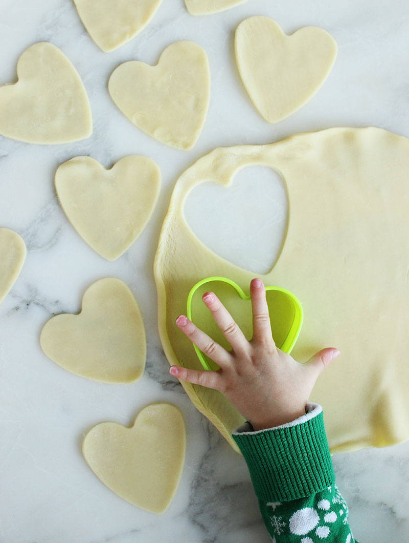 Cutting out a pie shell with cookie cutters for pop hearts.