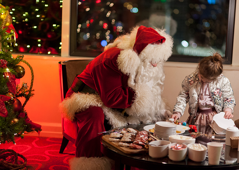 A little girl has hot chocolate with Santa.