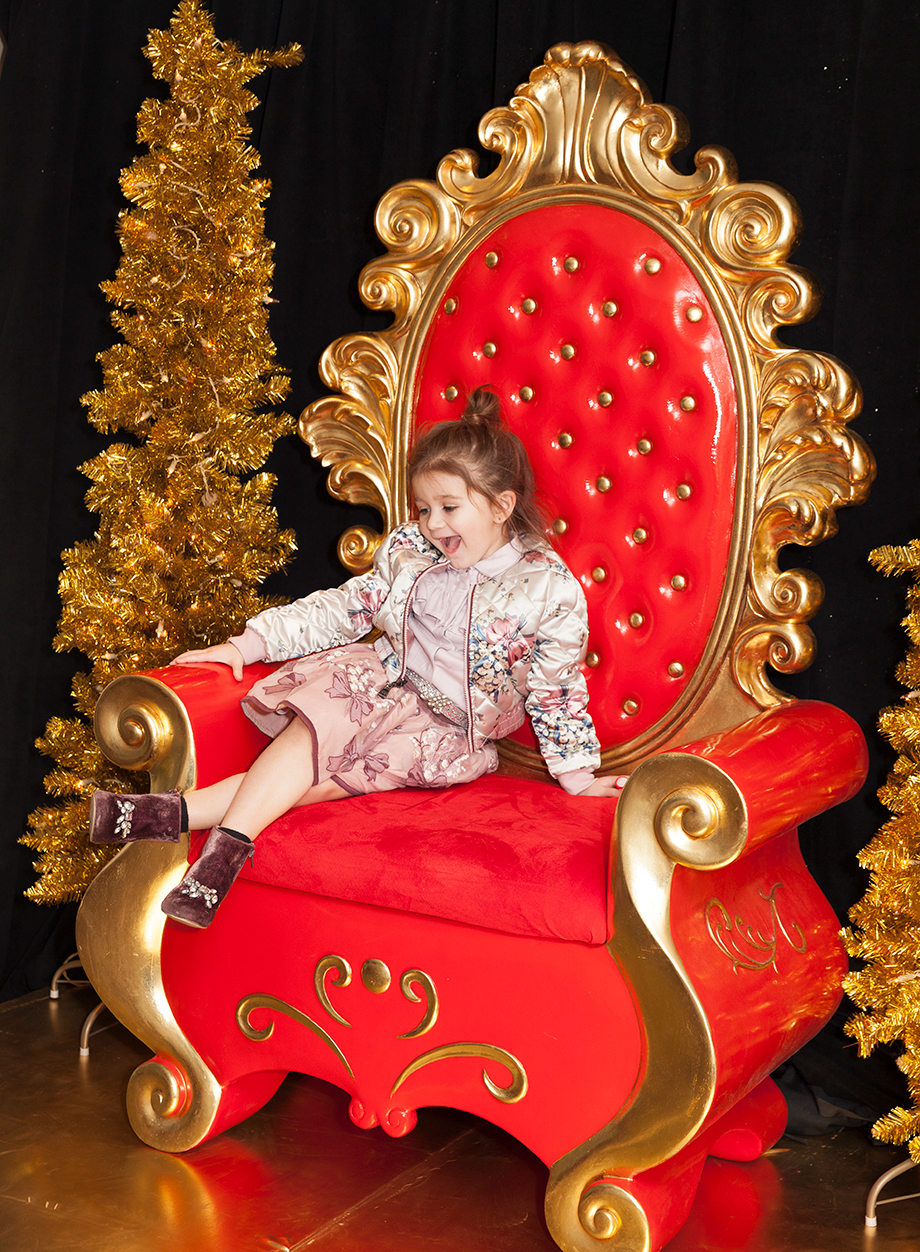 A toddler visits the Santa Suite in the Swissotel and sits in Santa's chair.