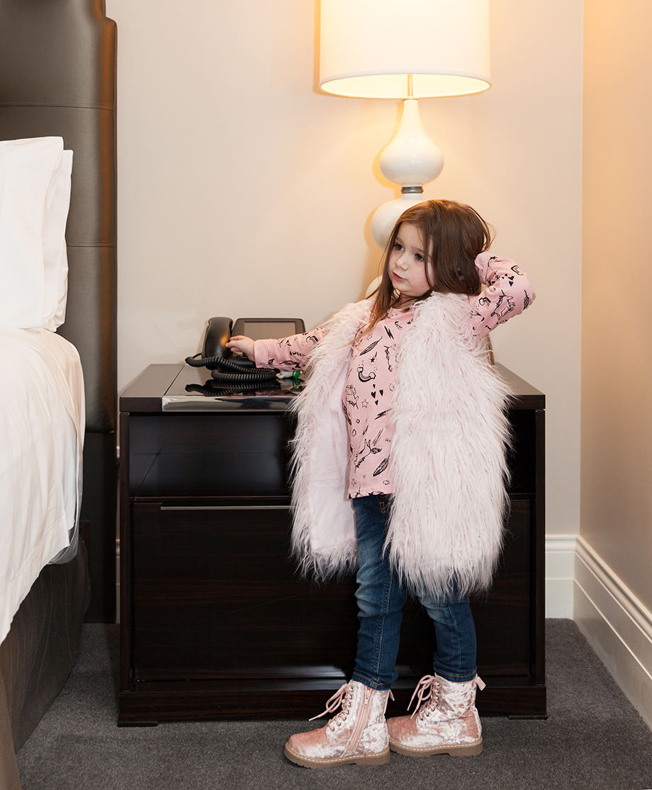 A toddler wearing a white faux fur vest and light pink crushed velvet boots.