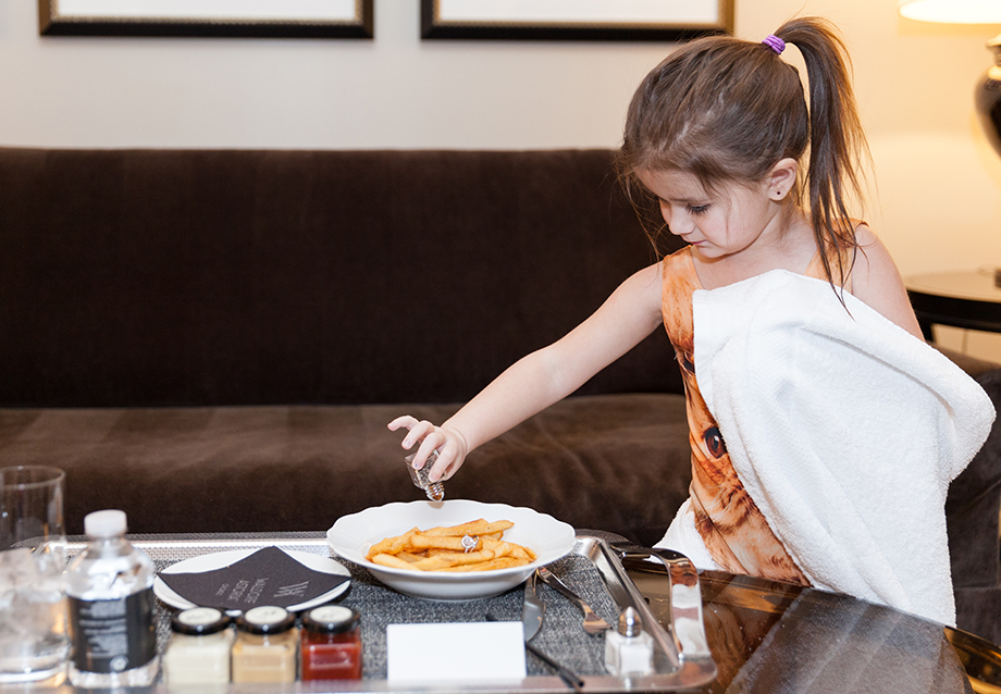 A toddler eats French fries at the Waldorf Astoria Chicago.
