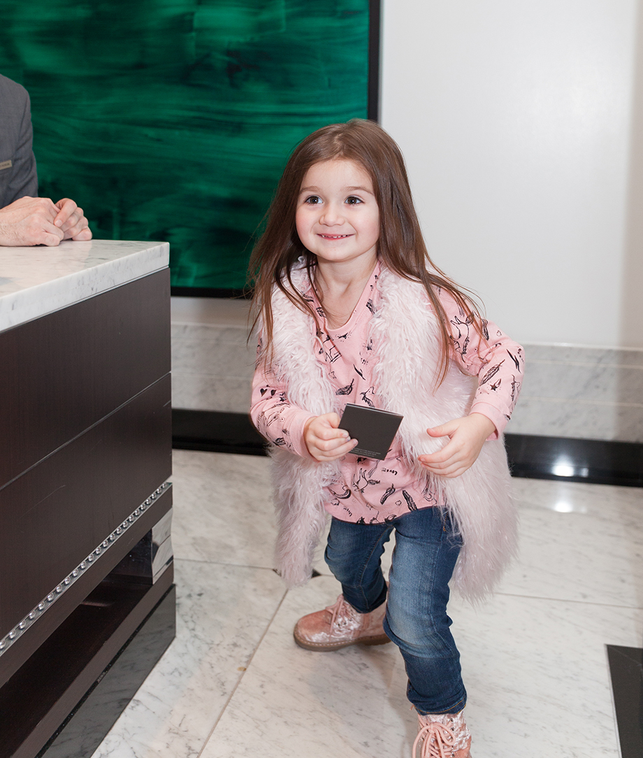 A toddler takes her room key for the Waldorf Astoria.