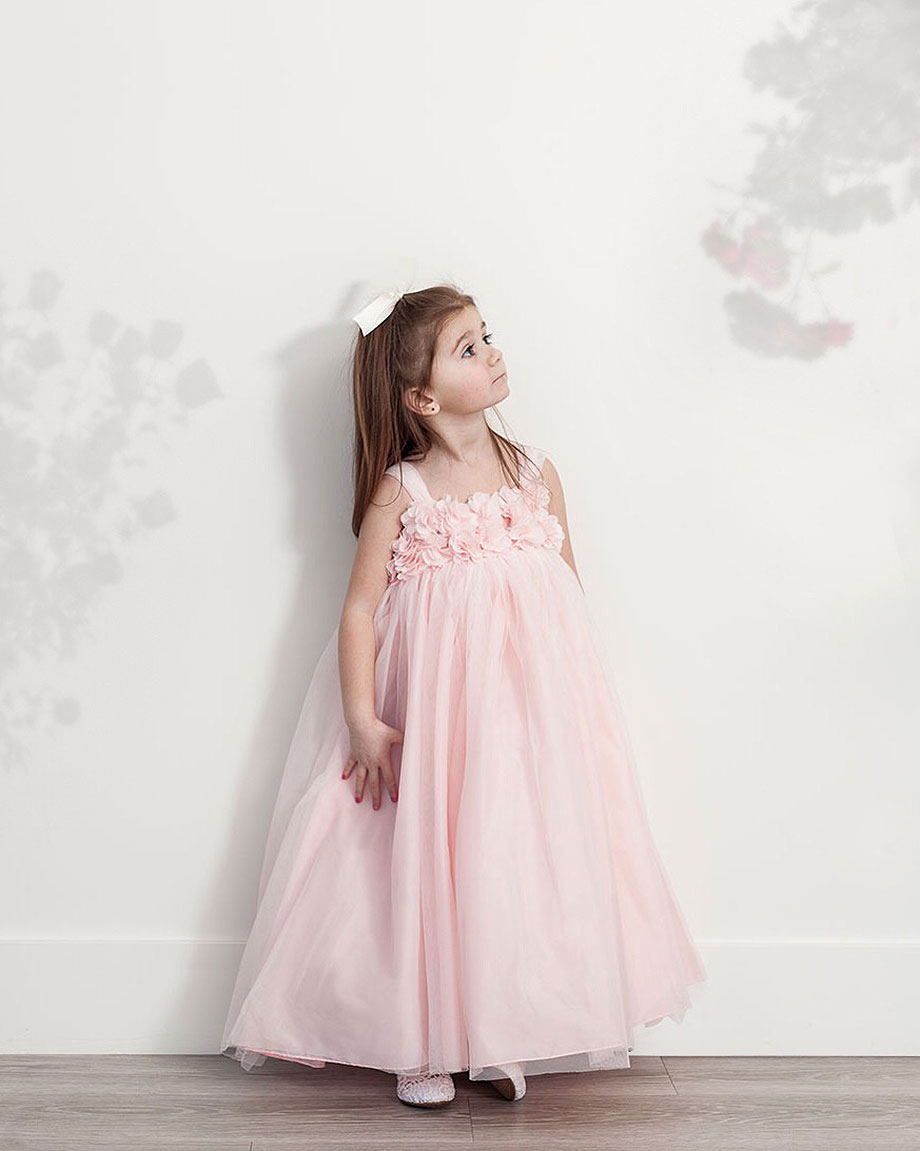 cc40dde6017 Zelda of Glitter and Bubbles stands against a wall in a pink dress from David s  Bridal 1. Flower girls love being ...