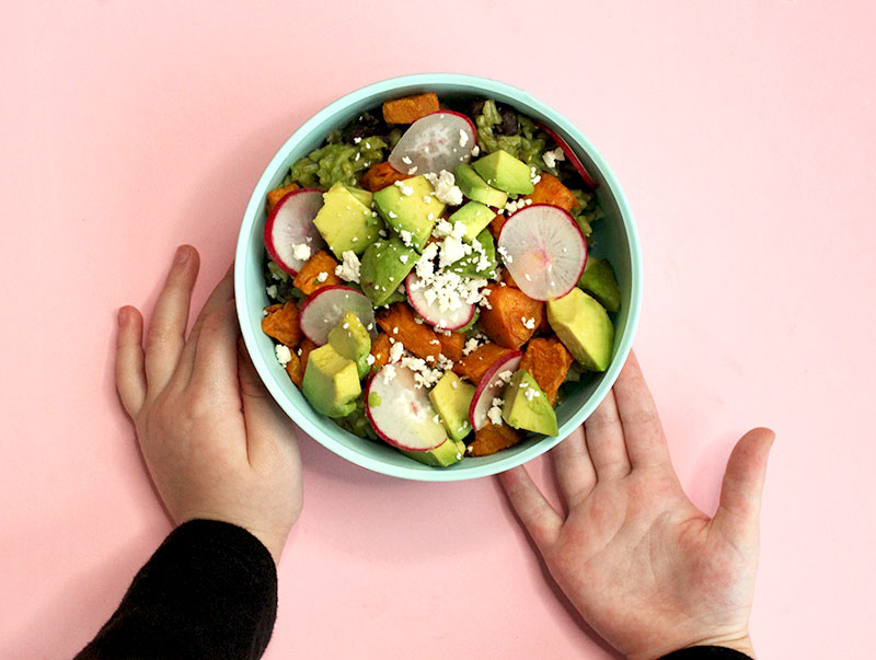 Zelda of Glitter and Bubbles holds a healthy green rice bowl with avocado and sweet potatoes.