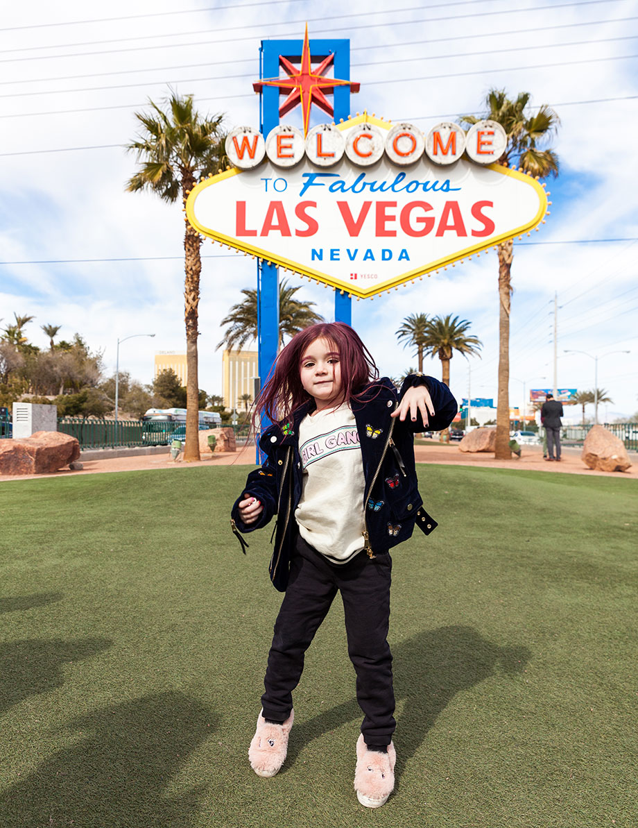 A little girl wearing a girl gang t-shirt jumps in front of the Las Vegas sign.