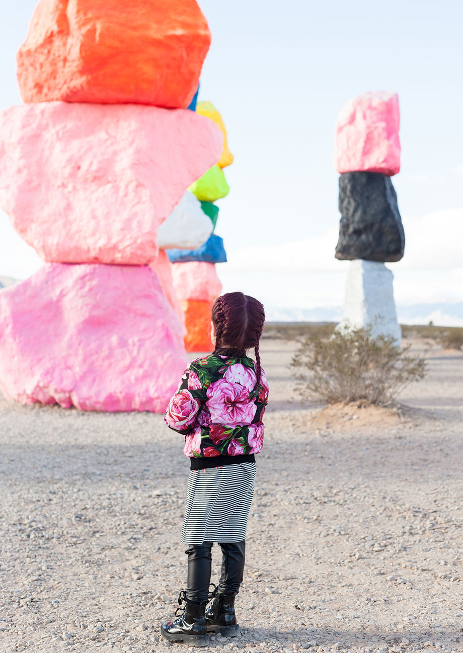 A toddler in a floral bomber jacket looks at Seven Magic Mountains in Las Vegas.