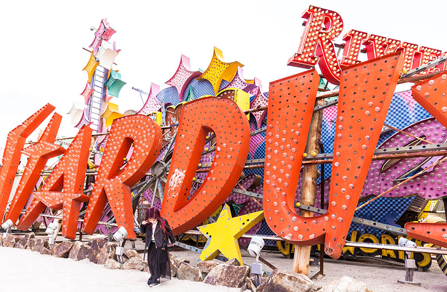 A toddler stands in front of the Stardust sign at the Neon Museum in Las Vegas.