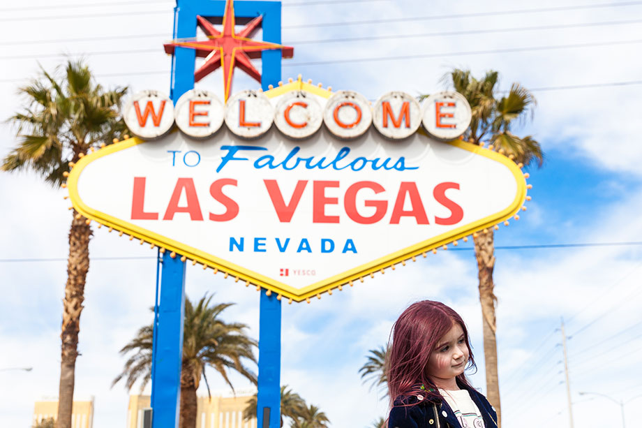 Zelda of Glitter and Bubbles walks in front of the Las Vegas sign.