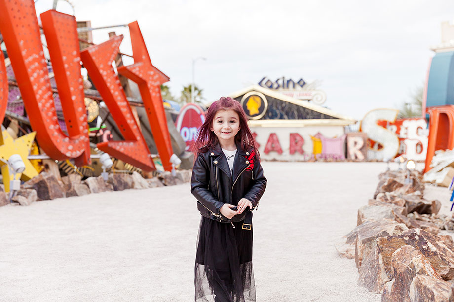 A toddler wears a leather jacket and a tulle skirt at the Neon Museum.