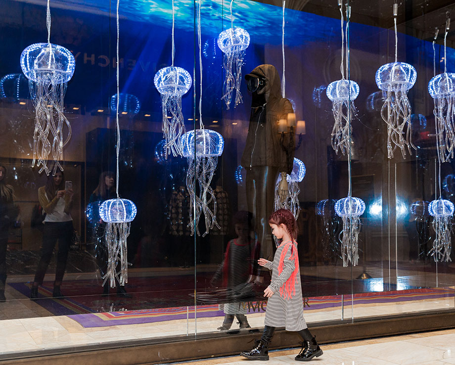 A little girl wearing a striped dress looks at jellyfish at The Wynn in Las Vegas.