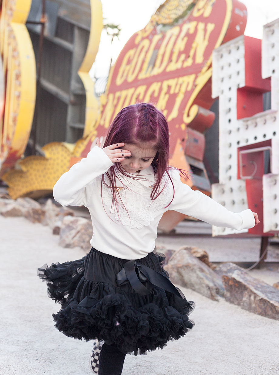 A pink haired toddler stands at the Neon Museum.