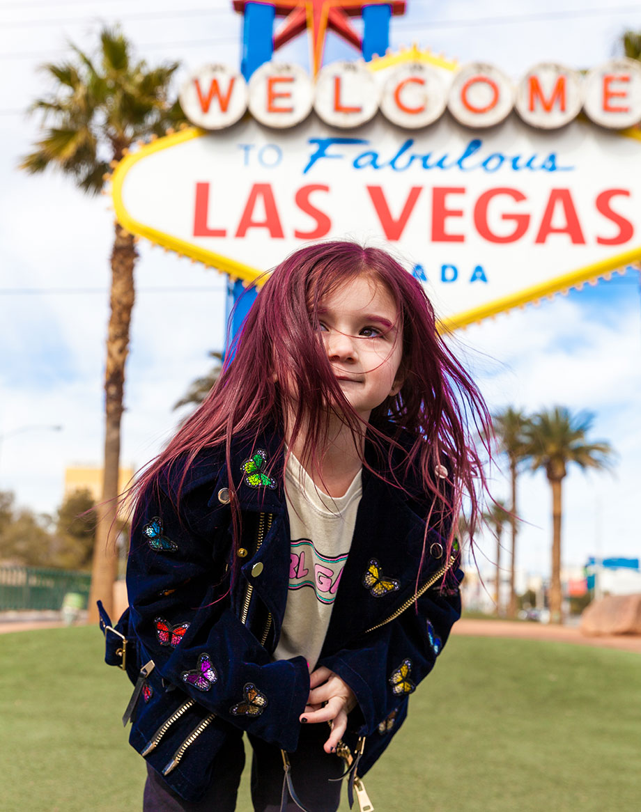A toddler with pink hair visits the Las Vegas sign in this kid-friendly Las Vegas Travel Guide.