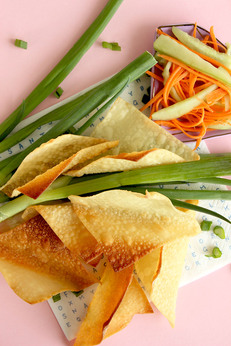 A collection of fresh vegetables and baked wontons on a pink backdrop.