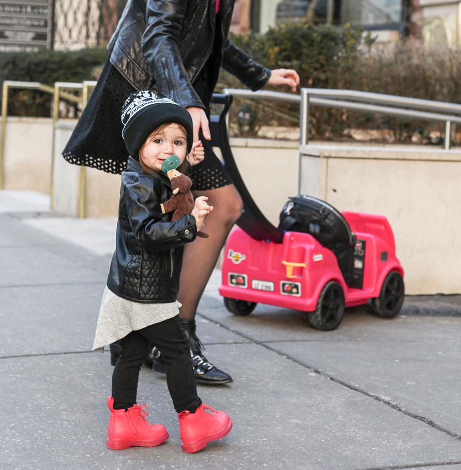 A toddler and her mother wearing matching black leather outfits.