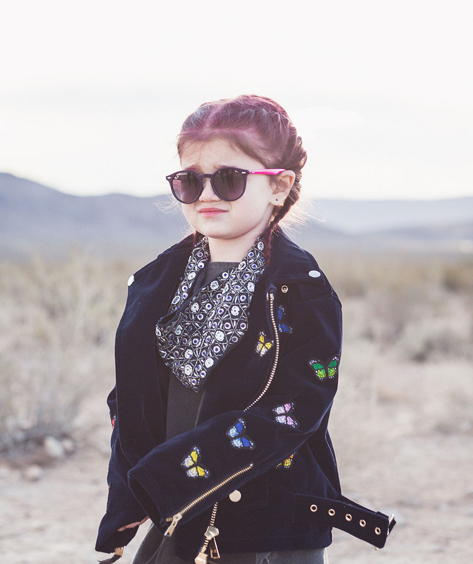 Zelda of Glitter and Bubbles stands in the desert of Las Vegas in a suede butterfly jacket.