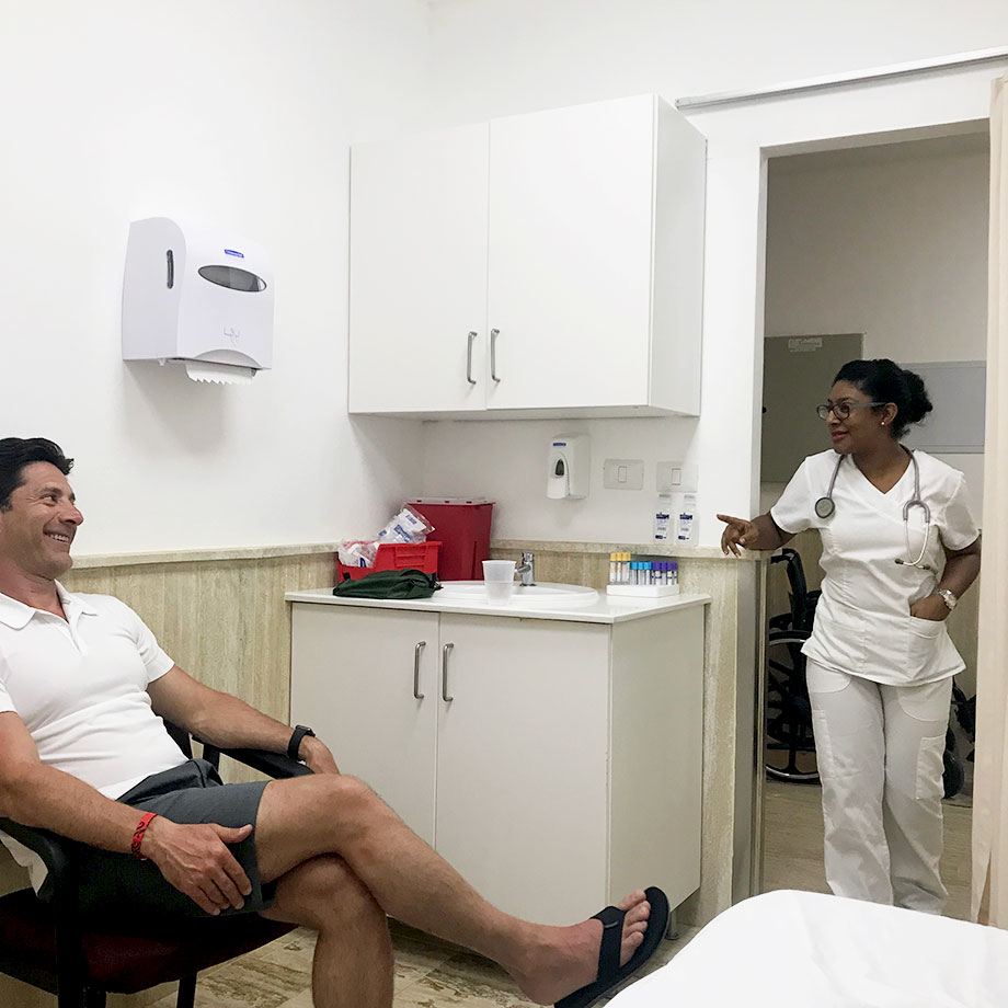A man sits in a doctor's office with a nurse in Punta Cana.