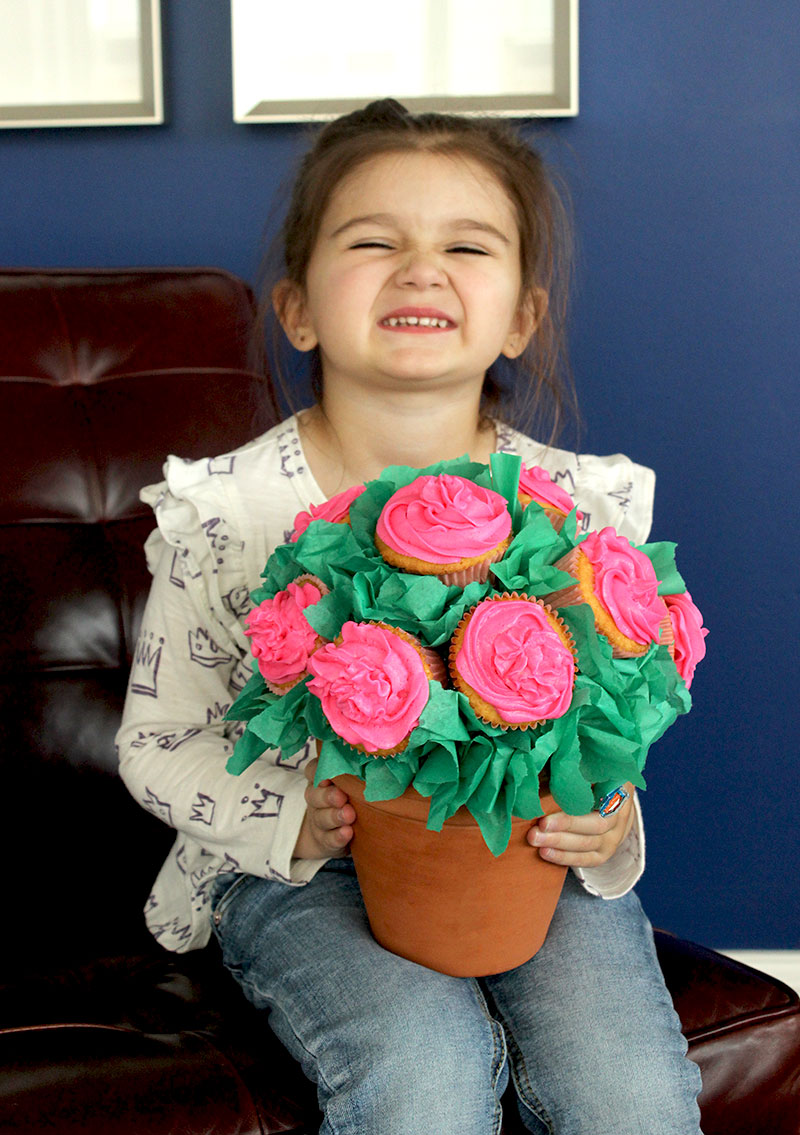 Zelda of Glitter and Bubbles holds a floral cupcake bouquet for Mother's Day.
