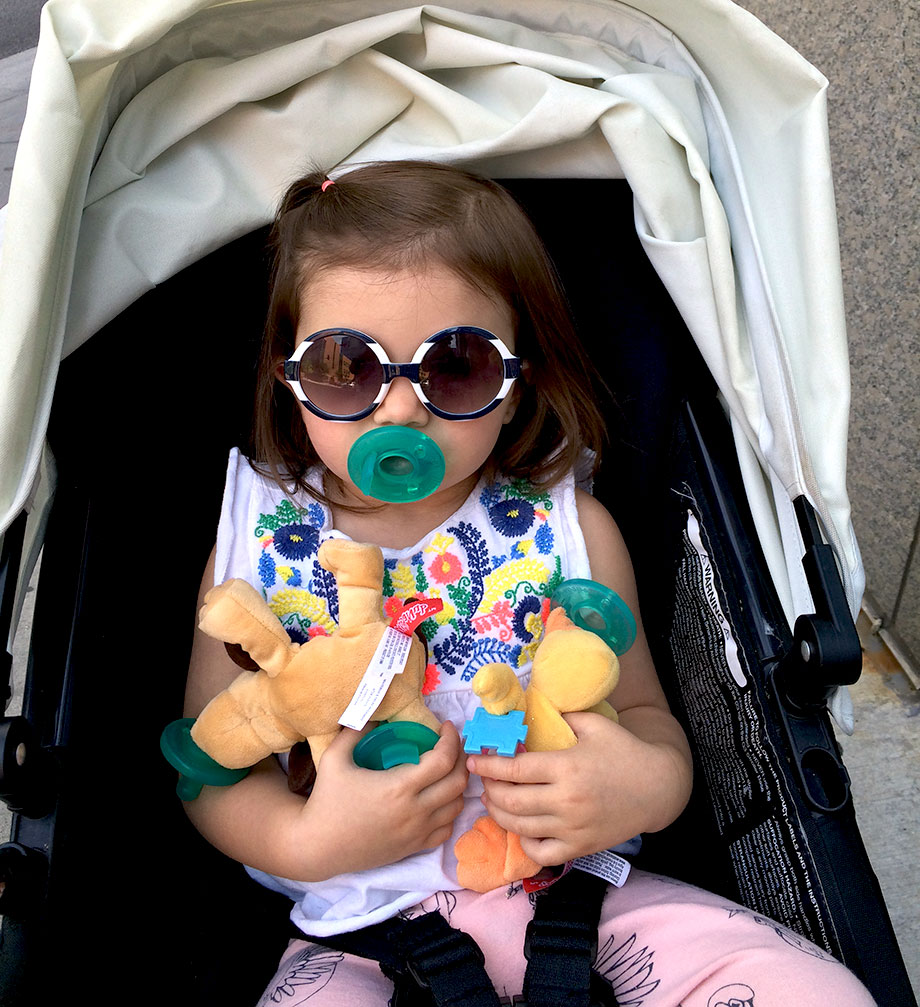 A toddler sits in a stroller with round frame sunglasses and pacifiers.