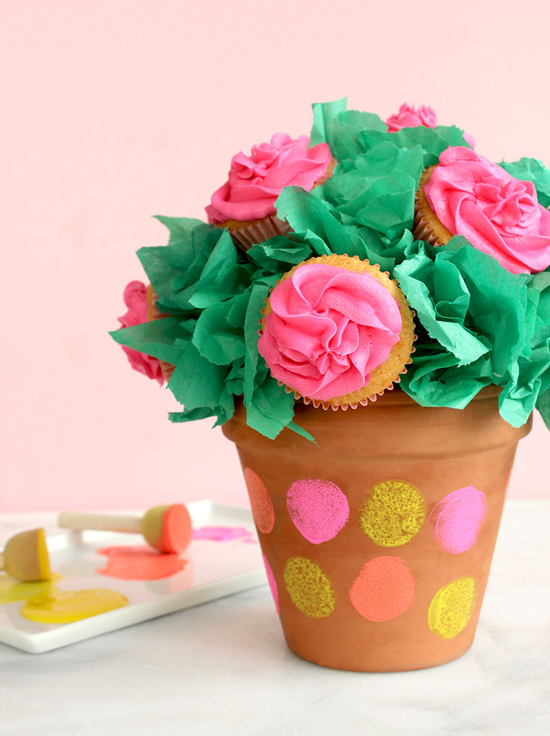 A vanilla buttercream cupcake bouquet with pink frosting sits in a painted terra cotta pot for Mother's Day.