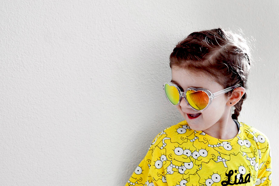 Zelda of Glitter and Bubbles wears her hair in a braid with yellow sunglasses.